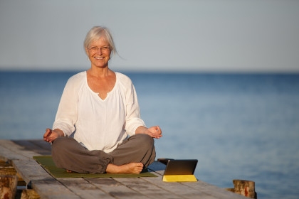 A mature woman doing yoga exercises on a pier with the help of her digital tablet